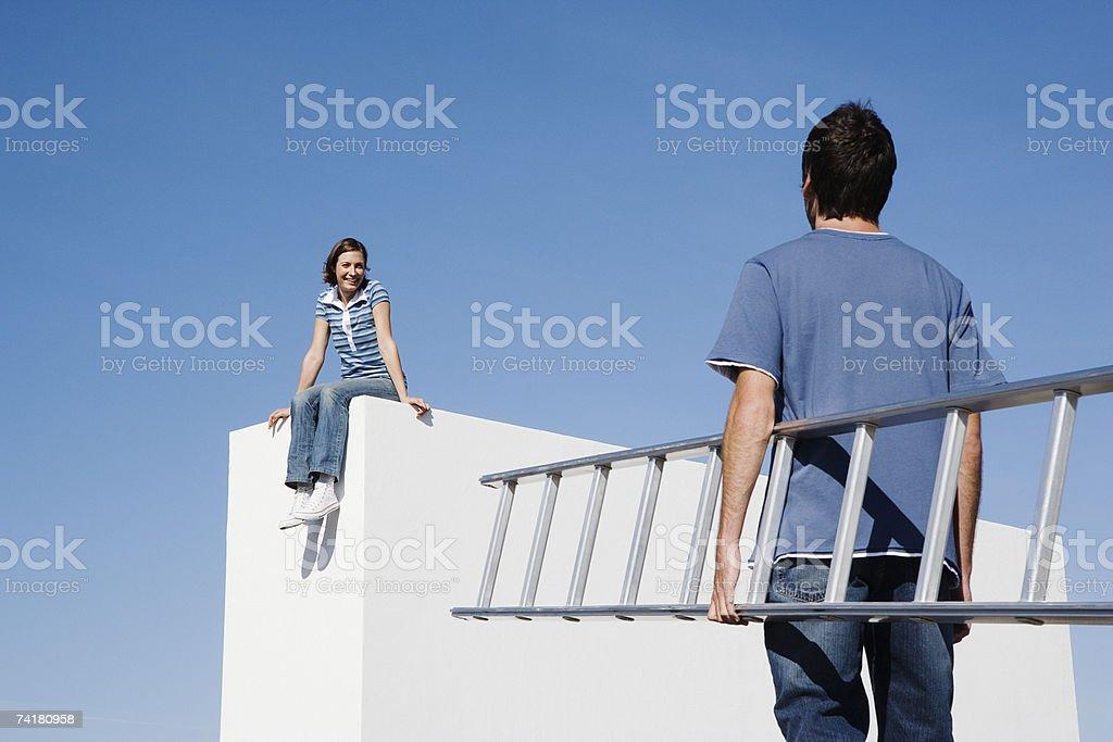 Mulher sentada na parede e homem com Escada ao ar livre foto de stock royalty-free