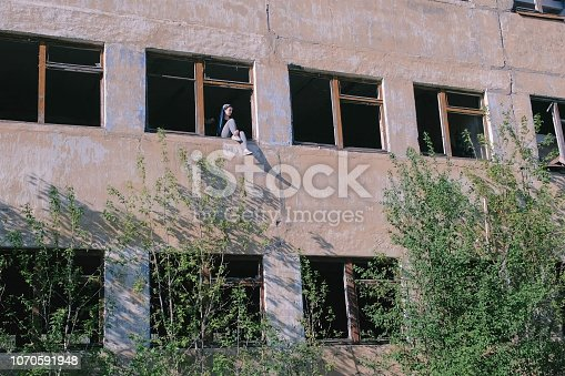 istock Woman sitting on window of destroyed multi-storey building with many broken windows. 1070591948