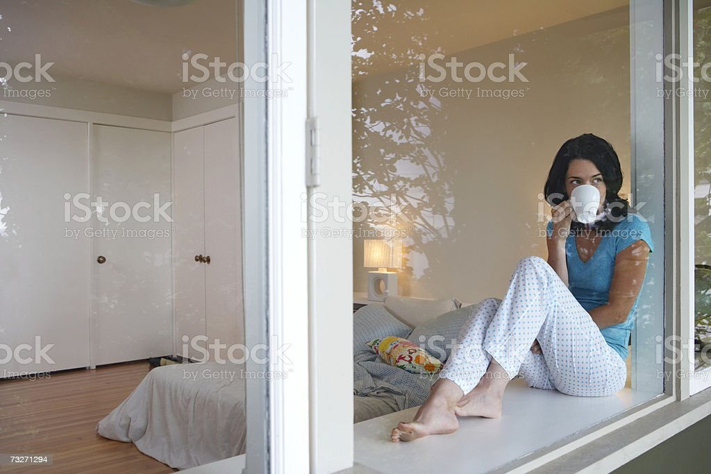 Woman sitting on window sill drinking coffee royalty-free stock photo