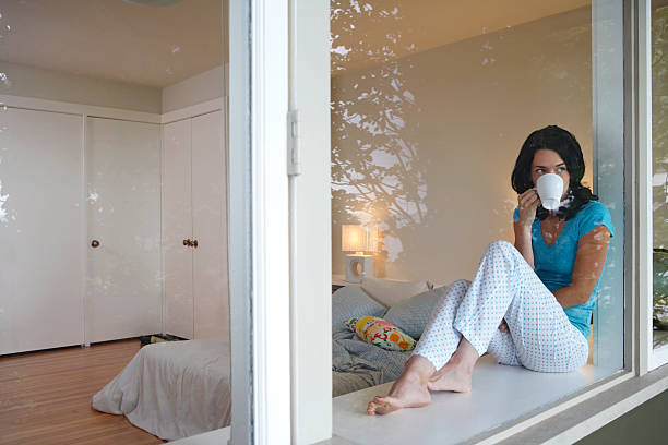 Woman sitting on window sill drinking coffee stock photo