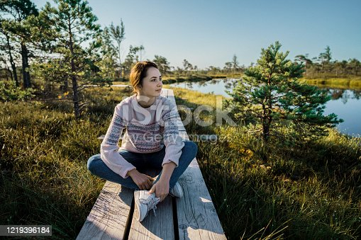 Young Caucasian woman  sitting  on wooden bridge  on swamp in Estonia