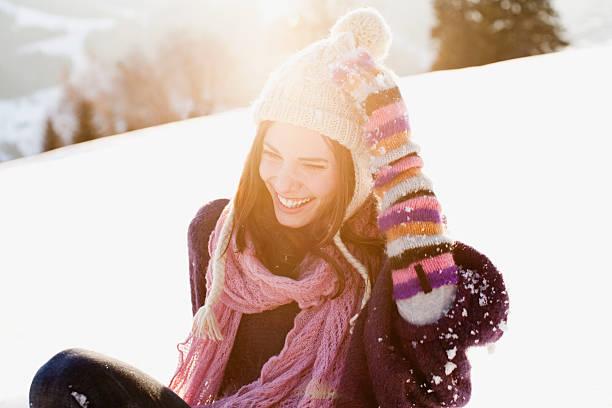 frau sitzt im freien im schnee - mützenschal stock-fotos und bilder