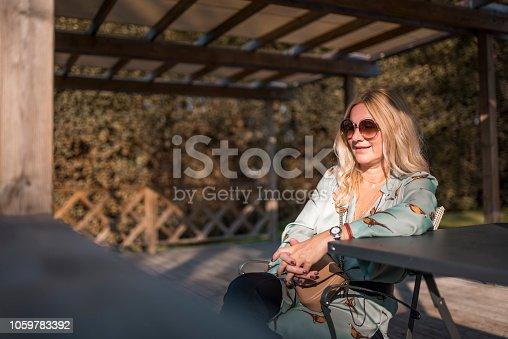 istock Woman sitting outdoors 1059783392
