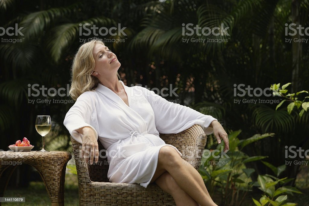 Woman sitting outside in robe, glass of wine stock photo