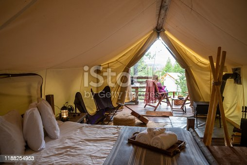 woman sitting outside luxury camping tent enjoying view of forest