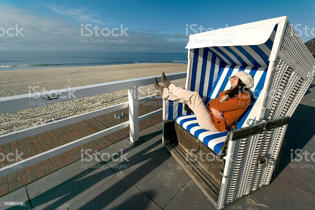 Woman sitting relaxed in beach chair at the coast stock photo