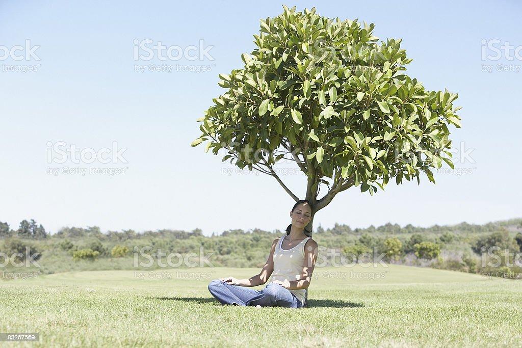 Femme assis à l'ombre sous un arbre photo libre de droits