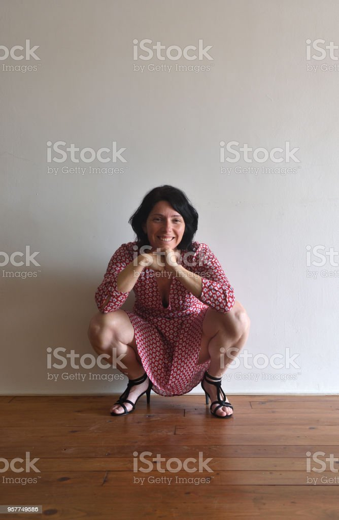 woman sitting squatting in front of ura wall stock photo
