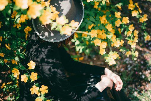 486439381 istock photo Woman sitting surrounded by flowers 1220378574