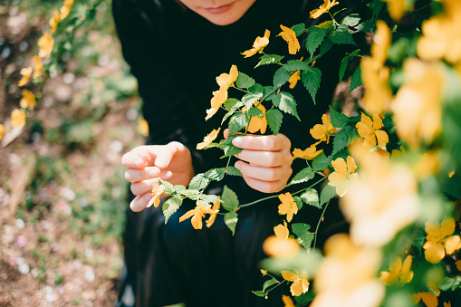486439381 istock photo Woman sitting surrounded by flowers 1220394854