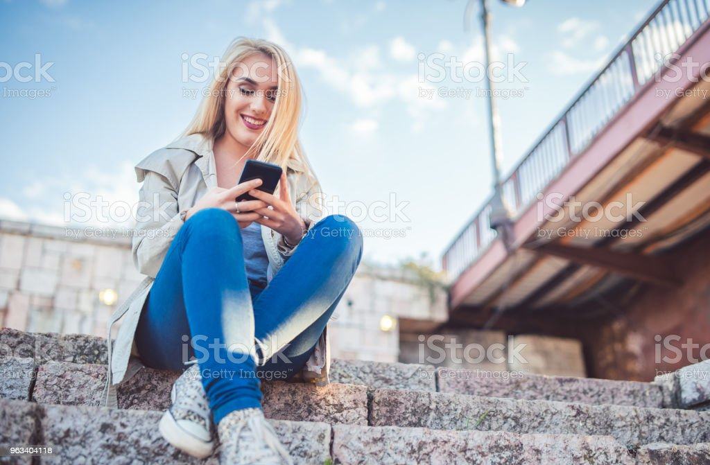 Woman sitting under the bridge and using mobile phone. - Zbiór zdjęć royalty-free (20-29 lat)