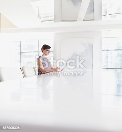 Woman sitting using tablet computer in room