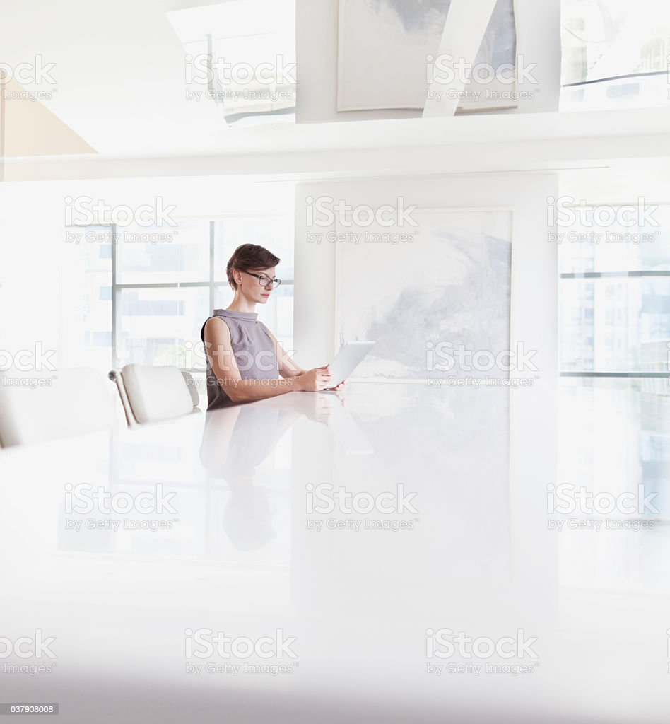 Woman sitting using tablet computer in room stock photo