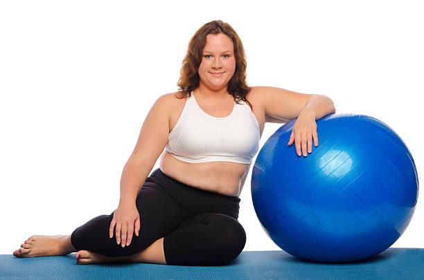 frau sitzt mit einem ball - damen leggings übergrößen stock-fotos und bilder