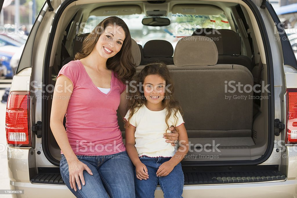 Woman sitting with a young girl in the back of a van royalty-free stock photo