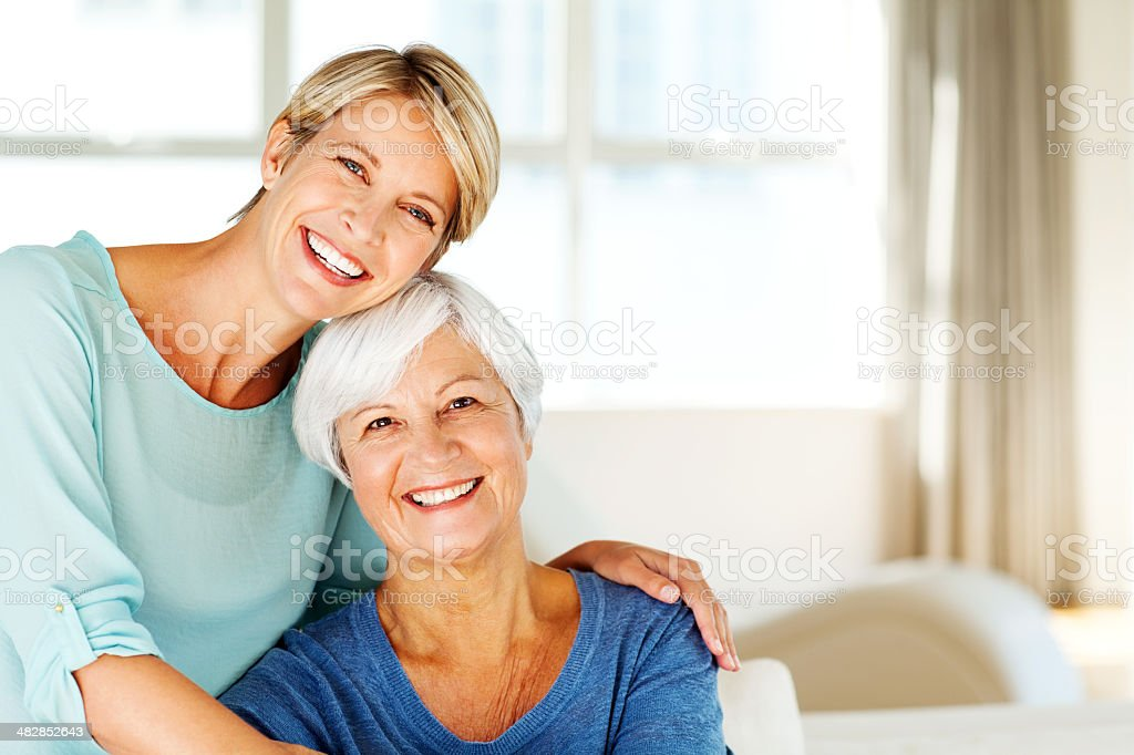 Frau sitzt mit Arme um Mutter im Wohnzimmer – Foto