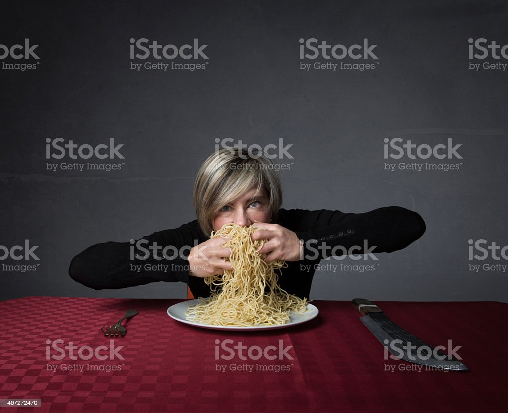 woman sitting with big forks and knifes stock photo