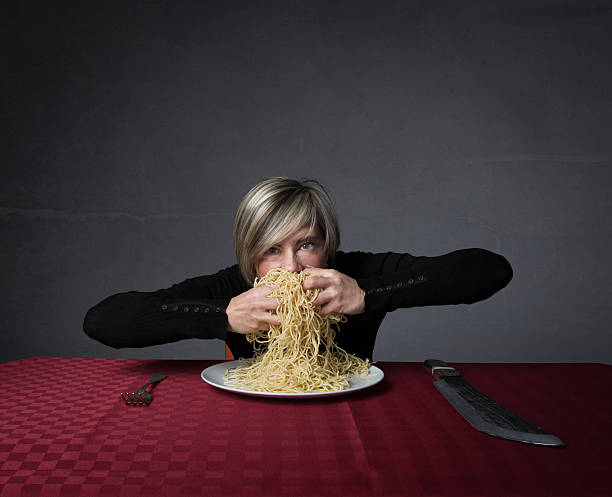 woman sitting with big forks and knifes