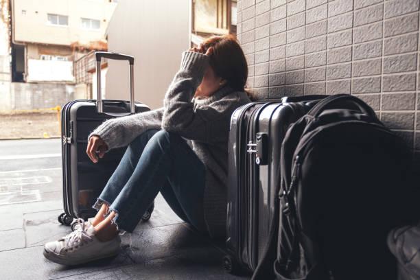 a woman sitting with feeling sad and lost while traveling - donna valigia solitudine foto e immagini stock