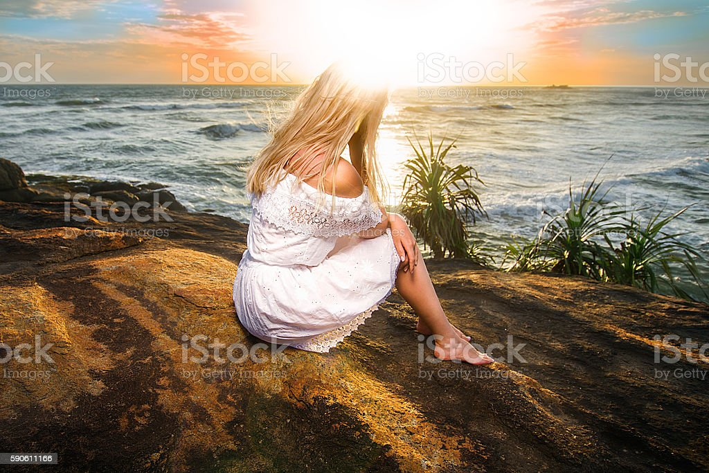 Woman sitting with her head in sun flare stock photo
