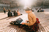 Woman sitting with laptop on Piazza del Campo in Siena