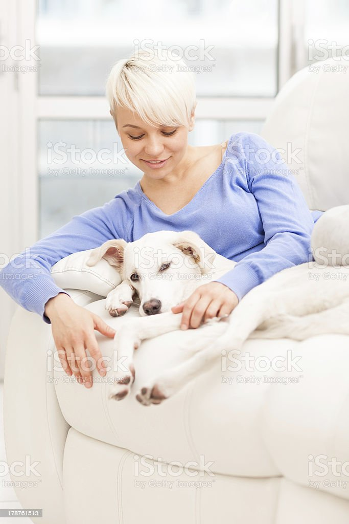 Woman sitting with young dog on the sofa stock photo