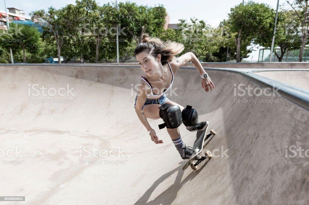 Woman skateboarding in skatepark stock photo