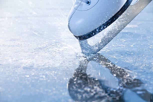 Woman skates braking ice, frazil flying around stock photo
