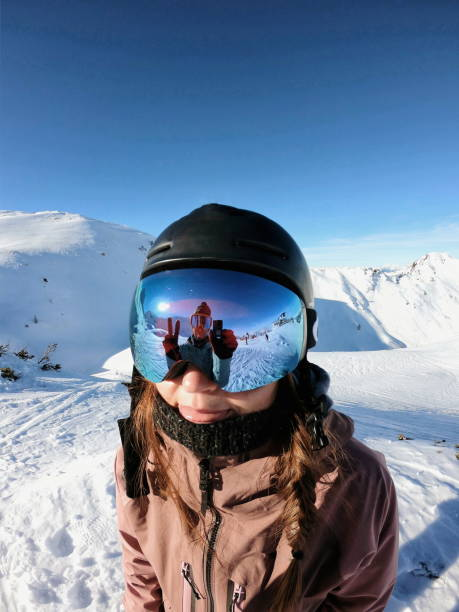 Woman skier and reflection in ski goggles stock photo