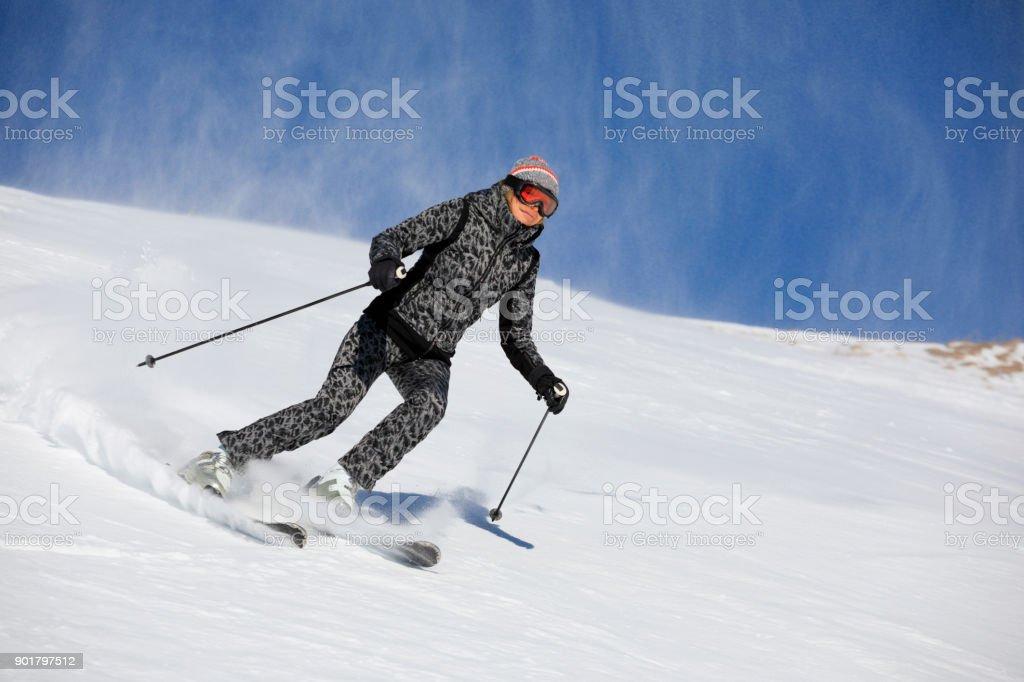 Woman skier skiing at sunny ski resort Amateur Winter Sports. High...