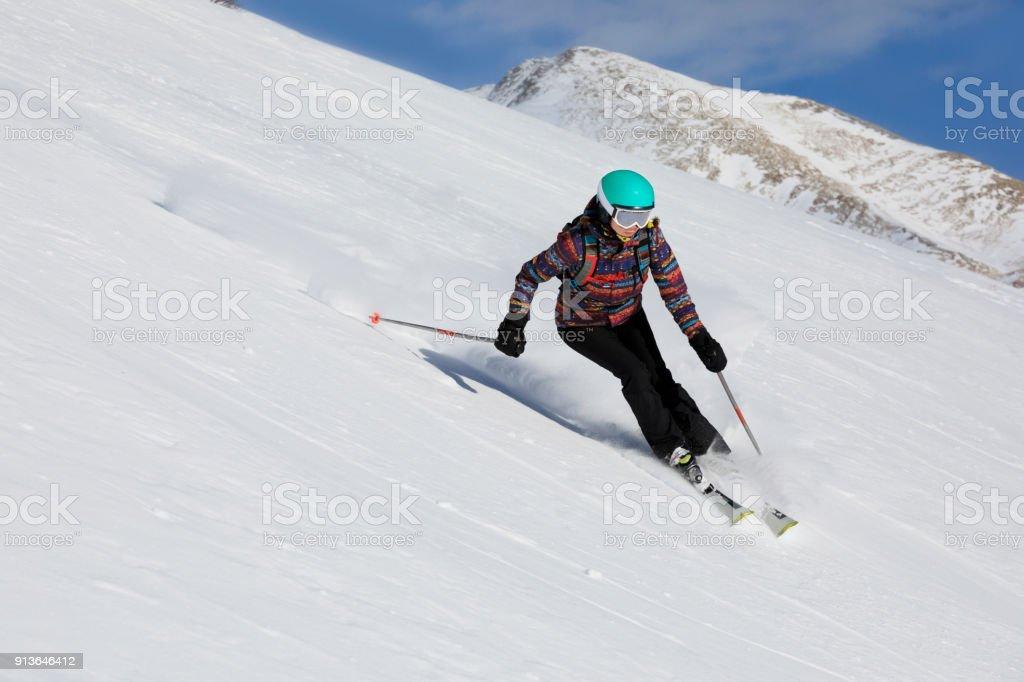 Woman skier skiing at sunny ski resort Amateur Winter Sports stock photo