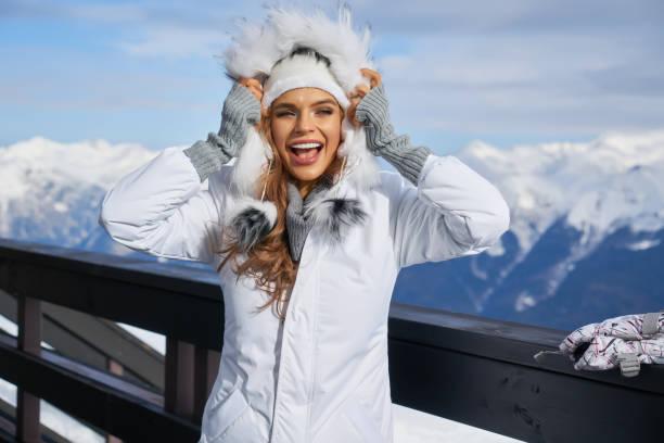 눈을 바라보며 카메라를 바라보고 있는 여자 스키어. 겨울 몽타인 배경 스톡 사진