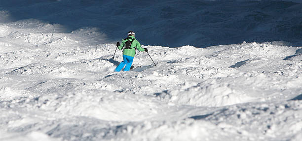woman skiing through steep moguls seen from above stock photo