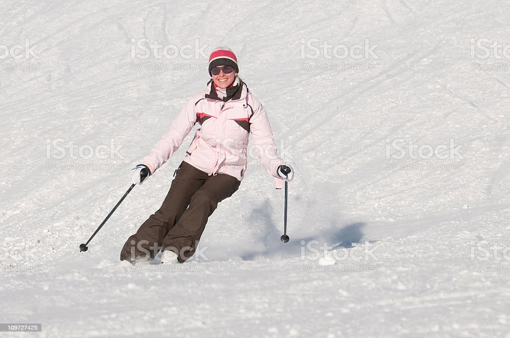 Woman skiing with carving ski down a slope royalty-free stock photo
