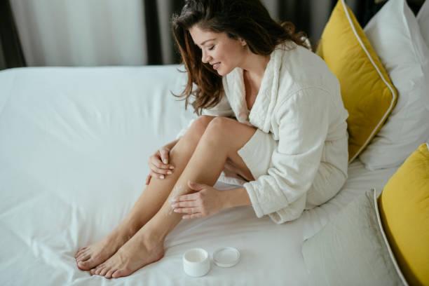 Frau, Hautpflege, Creme, Schlafzimmer. Frau kümmert sich zu Hause um ihre Beine – Foto