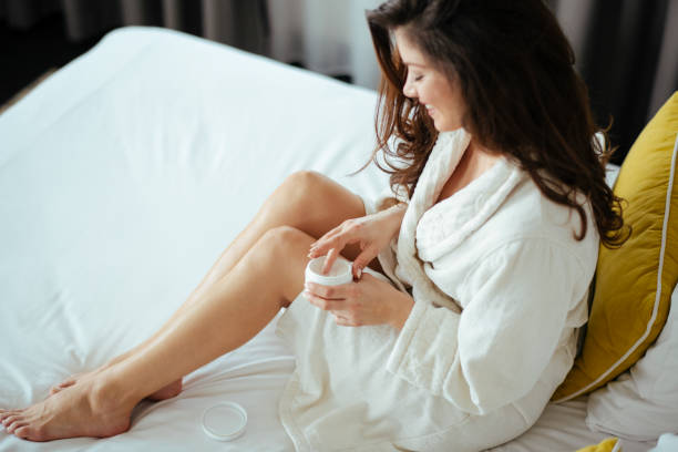 Woman, Skin care, Cream, Bedroom. Woman taking care of her legs at home stock photo