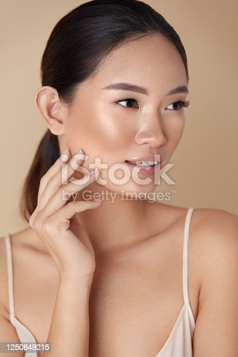 Woman. Skin Care For Perfect Look. Portrait Of Asian Model With Smooth Skin Touching Her Face And Looking Away. Female Enjoying Hydrated Skin After Daily Beauty Routine Or Cosmetology Treatment.