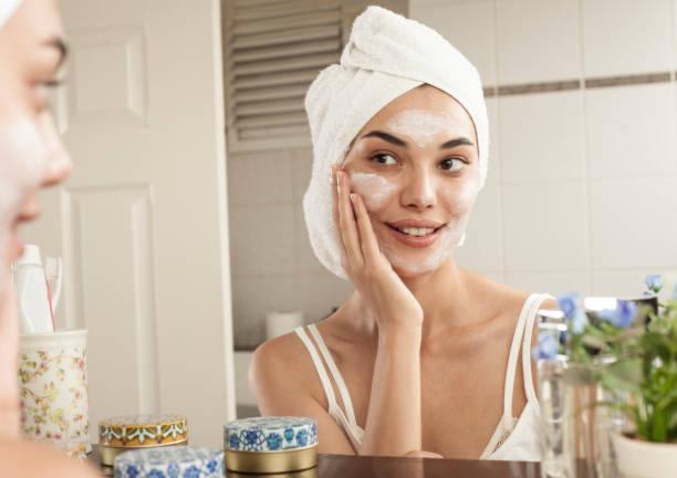 vrouw skincare op de badkamer - huidverzorging stockfoto's en -beelden