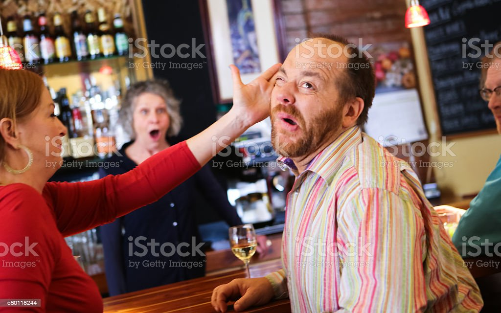 Woman Slaps Funny Man in Bar stock photo