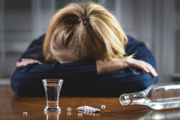 Woman sleeping after drug overdose and drinking vodka stock photo