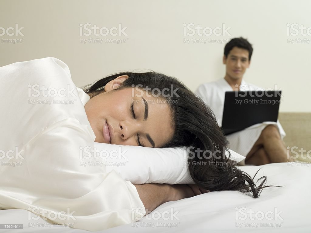 Woman sleeping and man with laptop royalty-free 스톡 사진