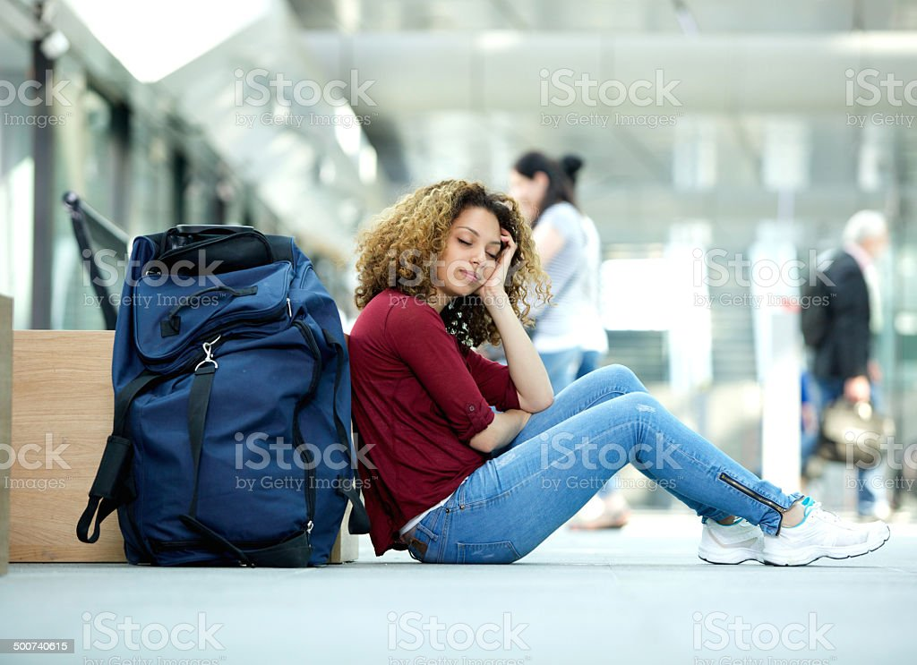 Woman sleeping at airport with luggage stock photo