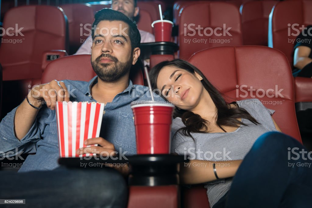 Woman sleeping at the movie theater stock photo