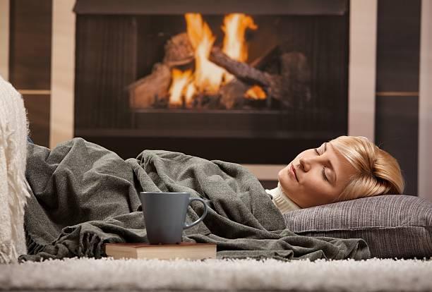 Woman sleeping beside fireplace stock photo