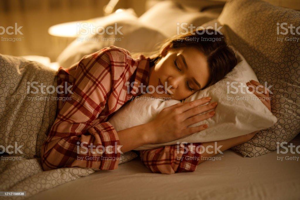 Frau schläft im Bett umarmt weicheweiße Kissen - Lizenzfrei Ansicht von oben Stock-Foto