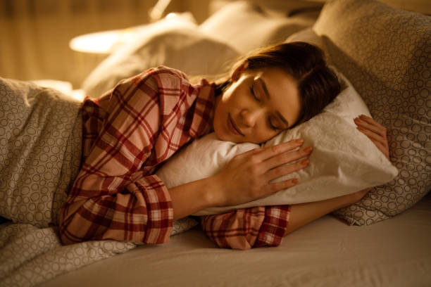 Woman sleeping in bed hugging soft white pillow stock photo