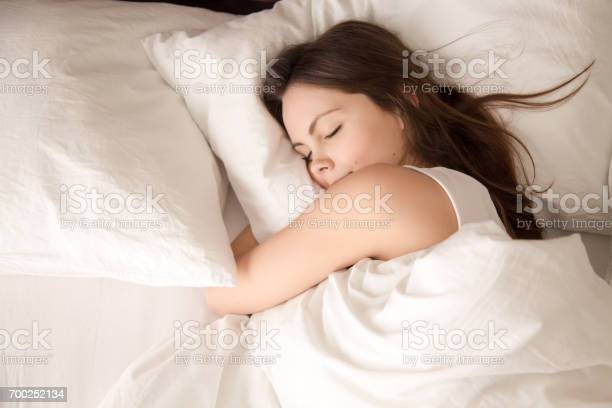Woman sleeping in bed hugging soft white pillow picture id700252134?b=1&k=6&m=700252134&s=612x612&h=t1xonzjneitlfwuakazabi5y 1jweja zujblt9snqq=