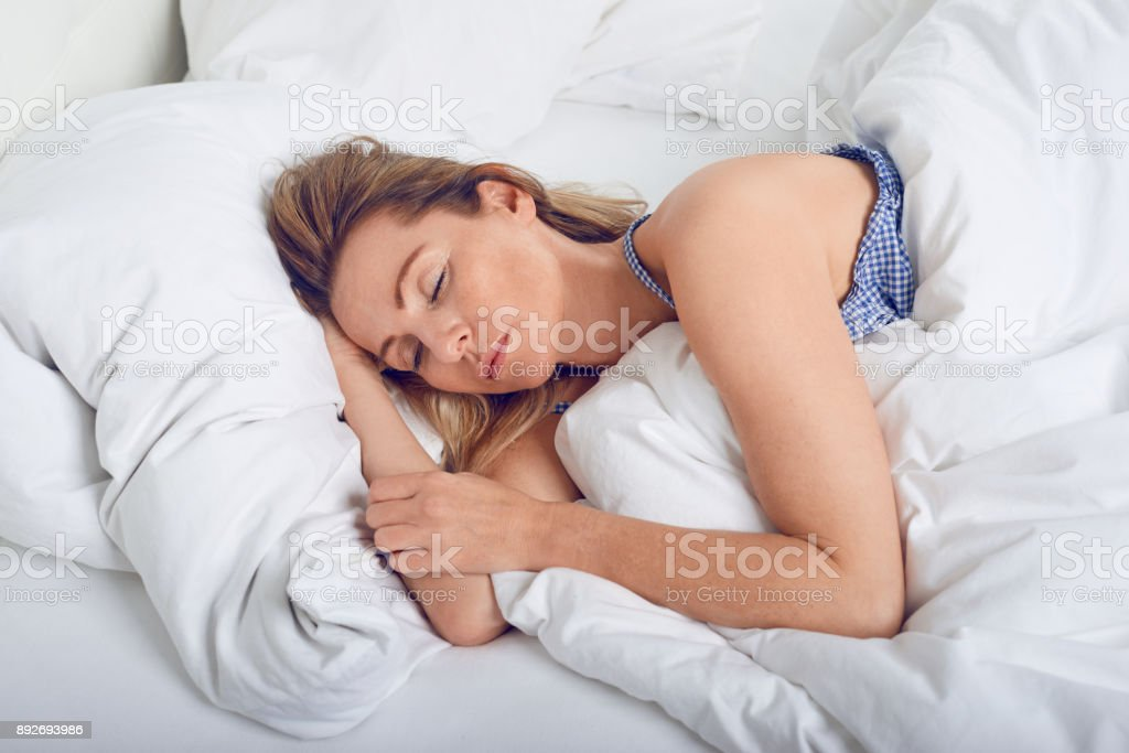 Woman sleeping in bed under quilt stock photo