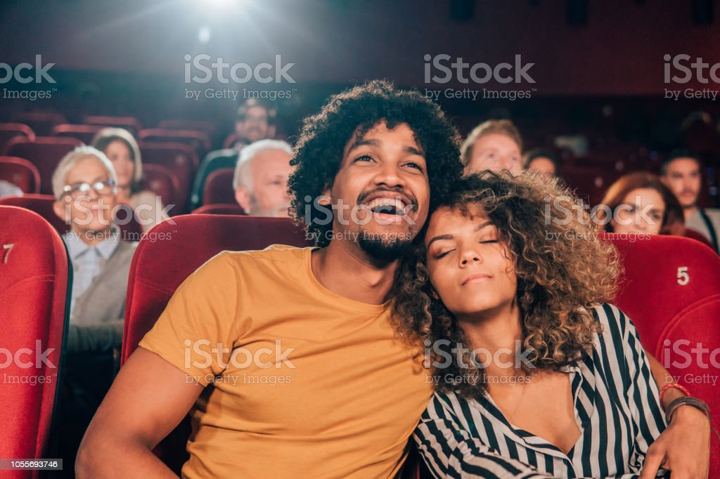 Woman sleeping in boyfriends arms at cinema stock photo