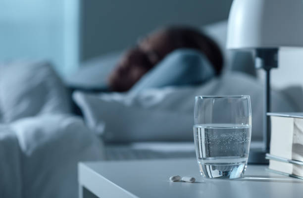 Mulher dormindo em sua cama à noite, o vidro na água e comprimidos no conceito de primeiro plano, medicamentos e tratamento - foto de acervo